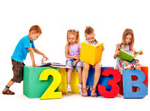 Children sitting at cube. Royalty Free Stock Image