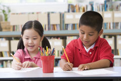 Children sitting at desk and writing in classroom Stock Photos