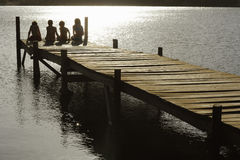 Children Sitting On Edge Of Jetty At Lake. Rear view of young boys and girls sitting on edge of jetty at lake Stock Photo