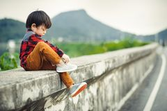 Children sitting on the gound and mountain is back. A children sitting on the gound and mountain is back royalty free stock images