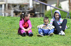 Children sitting on the grass Stock Photography