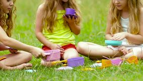 Children sitting on the grass playing with toys blurring the background. Slow motion. Close up. Children sitting on the grass playing with purple green yellow stock footage