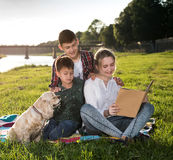 Children sitting on the grass and reading book Royalty Free Stock Images
