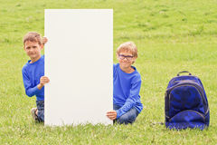 Children sitting on the grass with vertical blank white placard board outdoors Royalty Free Stock Photo