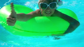 Children sitting on inflatable ring in swimming