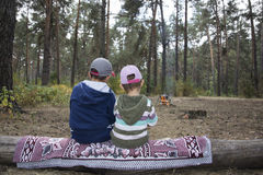 Children sitting on a log in the autumn forest and waiting when Stock Photography
