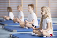 Children sitting in lotus pose. Group of children sitting in lotus pose on blue mats during a yoga class stock photography