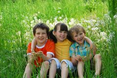 Children Sitting in Meadow Royalty Free Stock Images