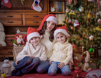 Children sitting with mother under Christmas tree in hats Stock Photo