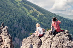 Children sitting on mountain peak. And looking at green valley Stock Photo