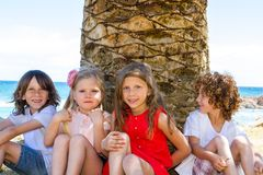 Children sitting next to palm tree. Stock Photos