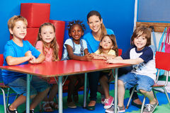 Children sitting with nursery teacher at table. Happy children sitting together with nursery teacher at table in kindergarten Royalty Free Stock Images