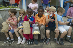 Children sitting at parade on curbside in central GA Stock Photography