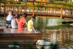 Children sitting in the park next to the pond. Stock Photo
