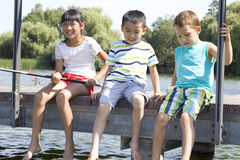 Children sitting on a pear an fish Stock Image