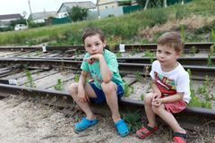 Children sitting on railway tracks. In summer royalty free stock images