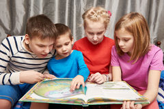 Children sitting and reading geography book royalty free stock image