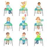 Children Sitting At School Desks In Class Stock Images