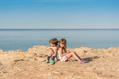 Children sitting at a sea shore. Yound children sitting alone with sad faces at a rocky sea shore stock image