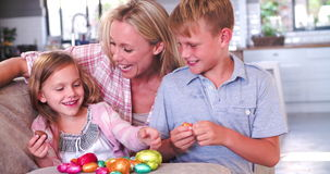 Children Sitting On Sofa With Mother Eating Easter Eggs stock video footage