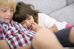 Children sitting in sofa playing games Stock Photography