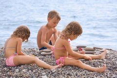 Children sitting on stony beach, creates pyramid Royalty Free Stock Images