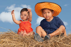 Children sitting on straw Royalty Free Stock Photography