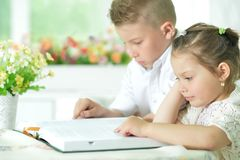 Children sitting at table and reading Stock Image