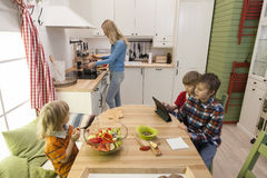 Children sitting at the table and waiting for their mother to cook dinner. Royalty Free Stock Photography