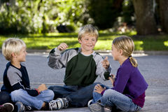 Children sitting and talking together on driveway Stock Image