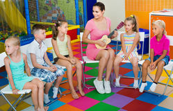 Children sitting with teacher and listening to music in class royalty free stock photography