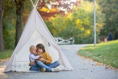 Children, sitting in a tent teepee, holding teddy bear toy with stock photo