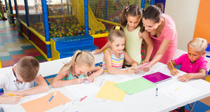 Children sitting together and drawing in class at school Stock Photography