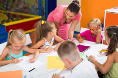 Children sitting together and drawing in class at school stock images