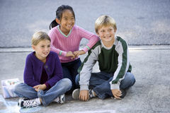 Children sitting together on driveway Stock Photo