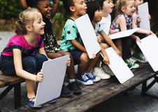 Children are sitting together holding placard Royalty Free Stock Photography