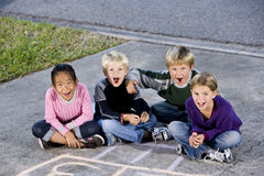 Children sitting together laughing on driveway Royalty Free Stock Image