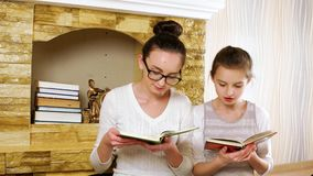 Children sitting together near fireplace at home and reading books, girls smiling and hugging stock video