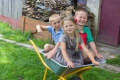 Children sitting in a wheelbarrow,happy children sitting in a wheelbarrow, two boys and a girl Royalty Free Stock Image