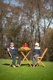 Children sitting at the wooden table on a picnic Stock Photo