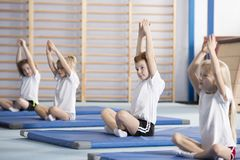 Children sitting in yoga pose. Children sitting in a yoga pose during PE classes at school stock photography