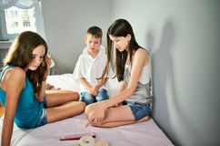 Children sittting on the bed in the room and looking on the digi Royalty Free Stock Photo
