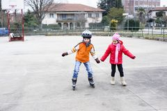 Children skate in the basketball field. Children, brother and sister, skate in the basketball field on a winter day Stock Images