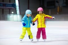 Children skating on indoor ice rink. Kids and family healthy winter sport. Boy and girl with ice skates. Active after school. Sports training for young child royalty free stock images