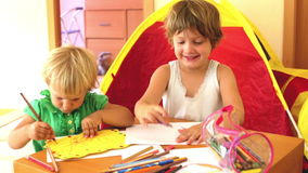 Children sketching on paper. Calm children sketching on paper in home interior stock footage