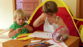 Children sketching with paper and pencils. In home interior stock video