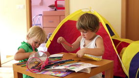 Children sketching with paper and pencils. Two little children sketching with paper and pencils in home interior stock video footage