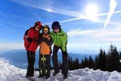 Children in ski clothes. Three happy children with ski clothes on snowy Alpine mountain with blue sky and sun in background Royalty Free Stock Photography