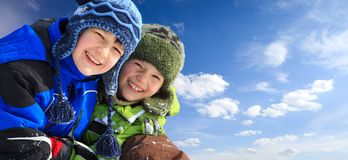 Children in ski clothing. Closeup of smiling young brothers in ski clothing and fur hats outdoors, blue sky and cloudscape background Stock Photo