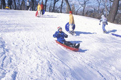 Children sled riding in Central Park, Manhattan, New York City, NY after winter snow storm Royalty Free Stock Photos